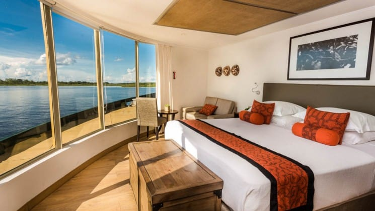Corner Suite with large bed, storage chest, couch, table and chairs, and floor-to-ceiling windows aboard Delfin III riverboat on Amazon River cruise