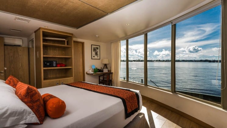 Corner Suite with large bed, storage shelves, desk, chair and floor-to-ceiling windows aboard Delfin III riverboat on Amazon River cruise