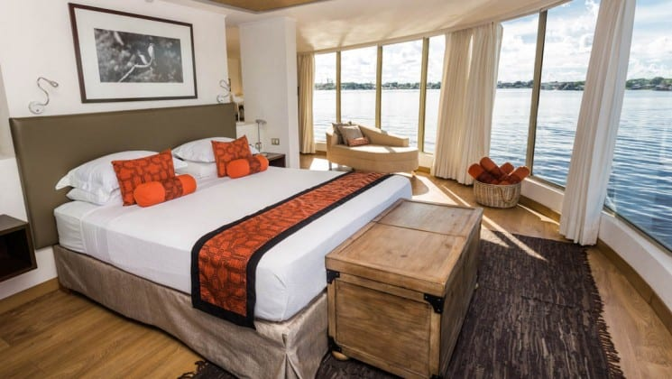 Owner's Suite with king bed, storage chest,chaise lounge and floor-to-ceiling panoramic windows aboard Delfin III riverboat on Amazon River cruise