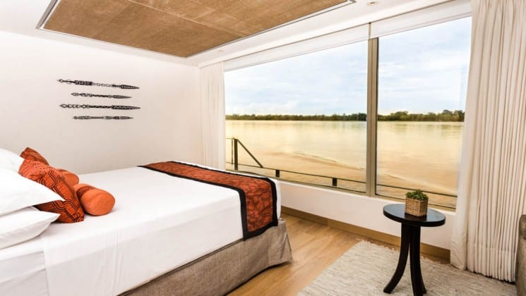 Suite with large bed, table and large picture windows with views of Amazon River aboard Delfin III riverboat