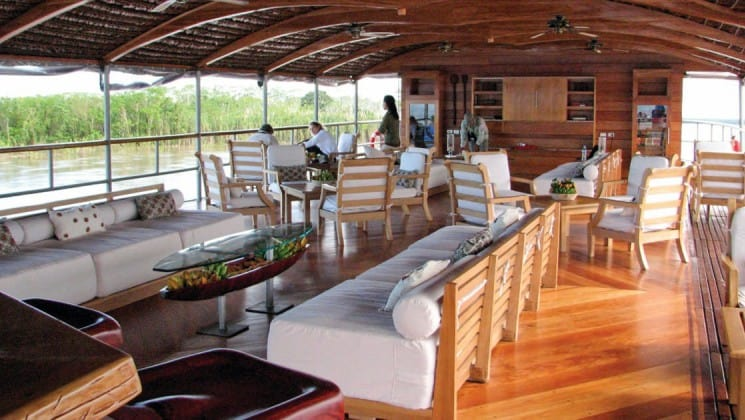 Al fresco lounge with couches, chairs and tables aboard Delfin II riverboat on Amazon River cruise