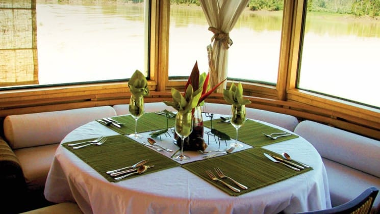 A corner table with place settings under a panoramic window in the Dining Room aboard Delfin II riverboat on Amazon River cruise