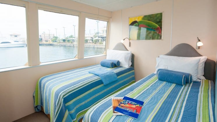 twin beds in front of 2 large windows aboard the panama discovery small ship