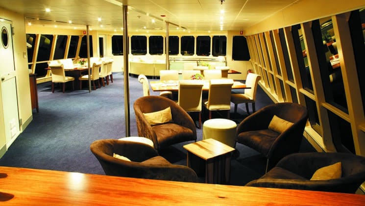 tables and chairs throughout a large window lined room aboard the panama discovery small ship