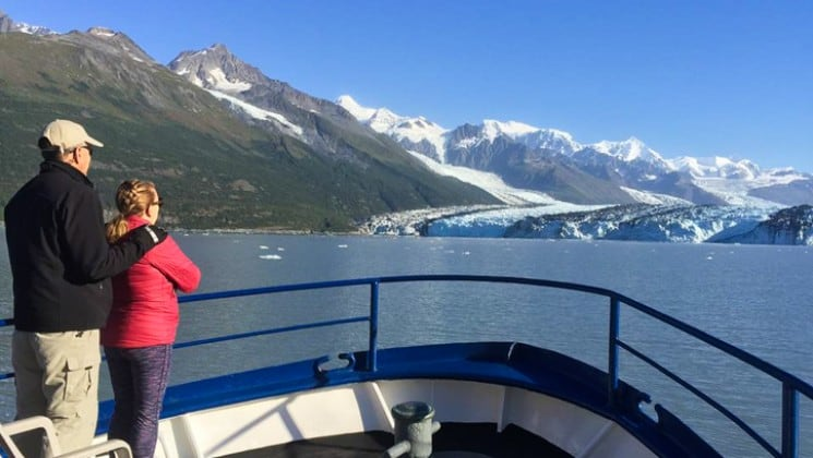 Man and woman at bow looking at distant mountains aboard Discovery classic working yacht in Alaska