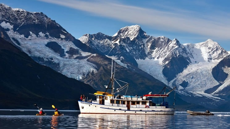 Distant view of full port side of Discovery yacht in Alaska, with kayakers near vessel and huge mountains in background