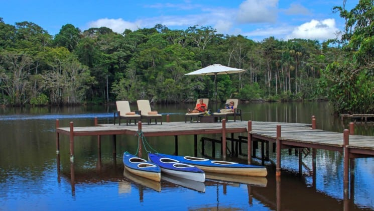 Three kayaks are tied to the dock, where lounge chairs are set up and guests relax under an umbrella, in front of La Selva Ecolodge, a sustainable, luxury accommodation in Ecuador