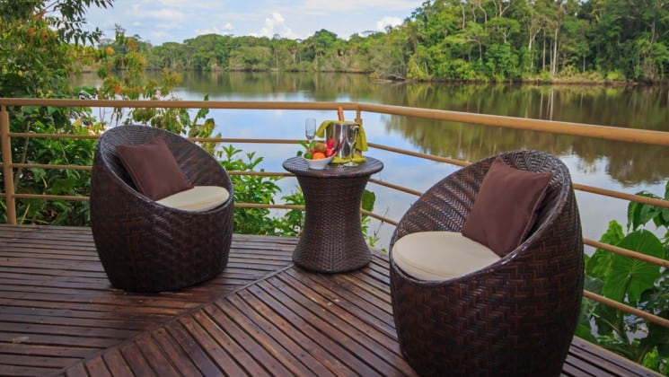 The private patio with lounge chairs and a lakeview attached to the scenic suite at La Selva Amazon EcoLodge, a sustainable, luxury accommodation in Ecuador.
