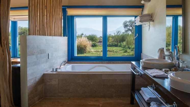 Jacuzzi tub beneath windows with distant mountain views at Explora Atacama Lodge in Chile