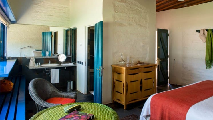 Bed, dresser, table, chairs and bench in the Tulur Room at Explora Atacama Lodge in Chile