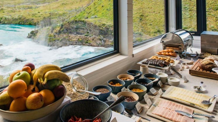 Breakfast buffet with fruit, meat, cheese, cereal, bread and pastries set on a table with lake and mountain views at Explora Patagonia Lodge in Chile