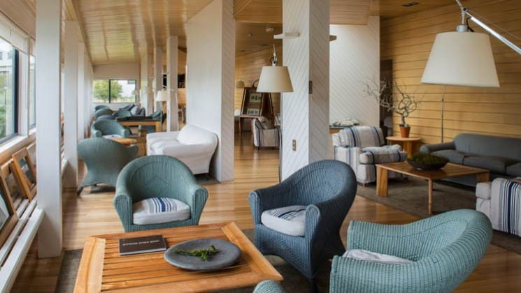 Couches and chairs set around tables near the windows of the common lounge at Explora Patagonia Lodge in Chile