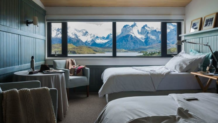 Two beds, a small table and two chairs in the Cordillera Paine Room at Explora Patagonia Lodge in Chile, with lake and mountain views
