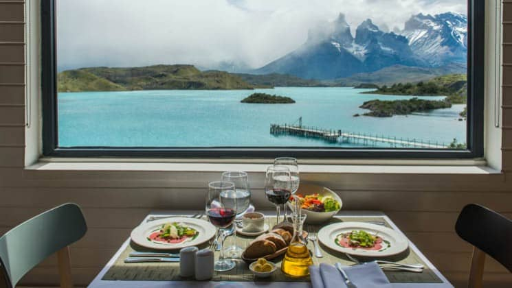 Lunch served with wine at a table for two at large window with lake and mountain views at Explora Patagonia Lodge in Chile