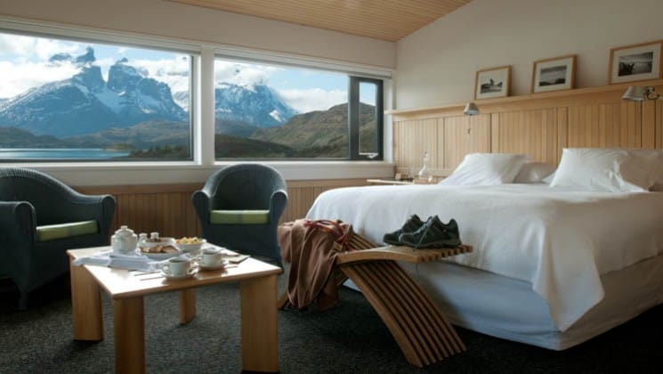 Large bed, table, two chairs, views to water and mountains from Exploradores Suite at Explora Patagonia Lodge in Chile