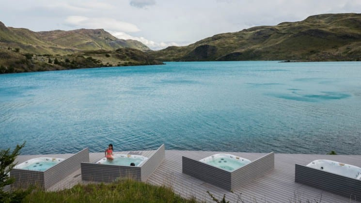 Four outdoor hot tubs placed on a deck with unobstructed views of the lake and mountains at Explora Patagonia Lodge in Chile