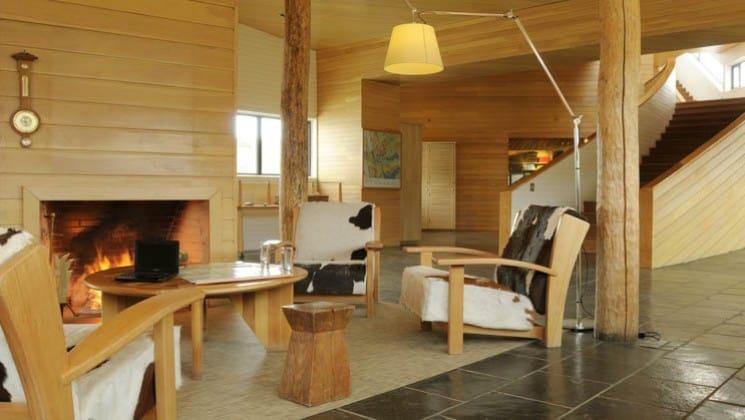 Chairs and a coffee table set up in front of a fireplace in the lounge area at Explora Patagonia Lodge in Chile