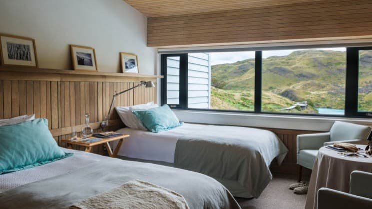 Mountain and lake views from the Salto Chico Room with two beds, a small table and two chairs at Explora Patagonia Lodge in Chile