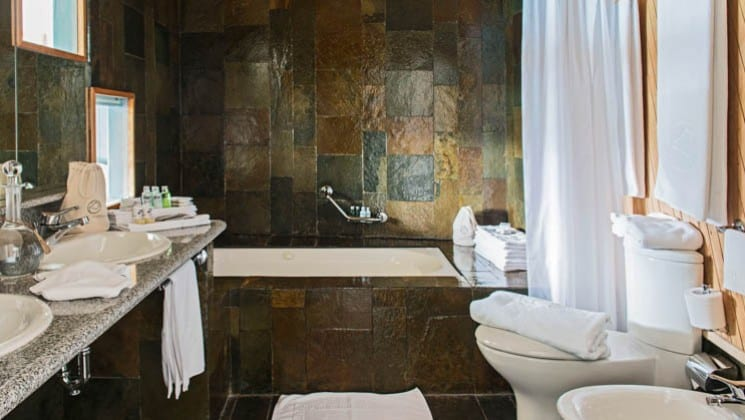 Jacuzzi, double sink, mirror, toilet and artisan tile work in the bathroom of the Exploradores Suite at Explora Patagonia Lodge in Chile