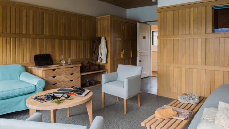 Wood finishings, a loveseat, a table and two chairs in the Exploradores Suite at Explora Patagonia Lodge in Chile