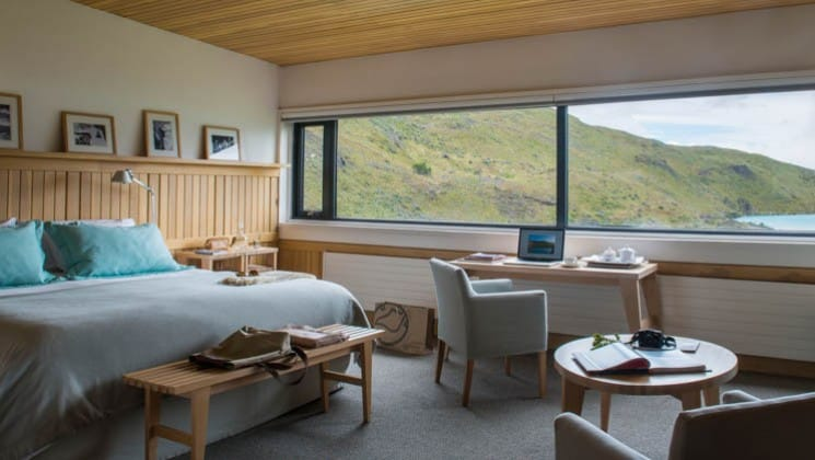Large bed, writing desk, small table and two chairs in Exploradores Suite looking out to Lake Pehoe at Explora Patagonia Lodge in Chile