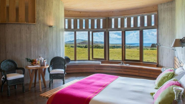 Bed, table, two chairs and window bench with ocean views in Raa Suite at Explora Rapa Nui Lodge on Easter Island