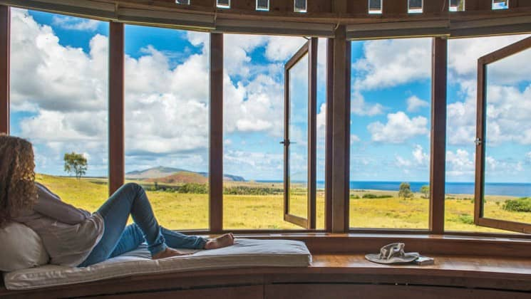 Woman sitting on window bench in Raa Suite at Explora Rapa Nui Lodge on Easter Island, with views to the ocean