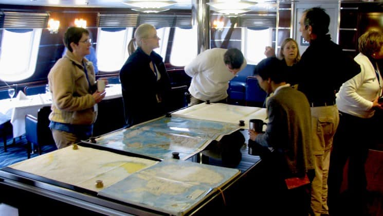 Passengers explore charts and maps in the Chart Room of National Geographic Explorer polar expedition ship