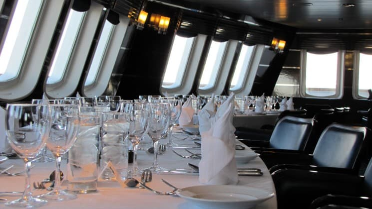 Dining table set up in Chart Room where guests take turns dining with the captain aboard National Geographic Explorer polar expedition ship