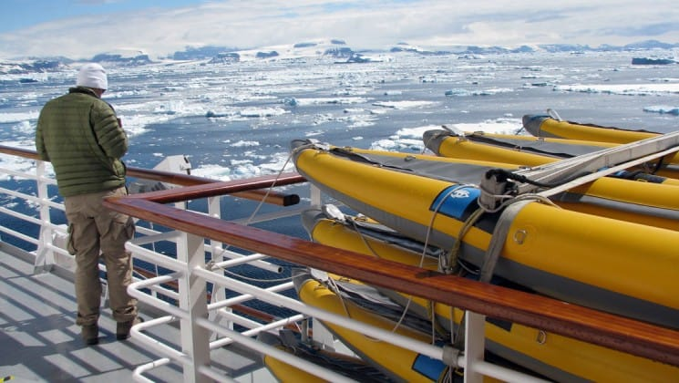 Man stands on deck beside kayaks stored for off-vessel exploration aboard National Geographic Explorer polar expedition ship