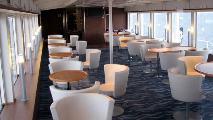 Tables and chairs in the window-lined Observation Lounge aboard National Geographic Explorer polar expedition ship