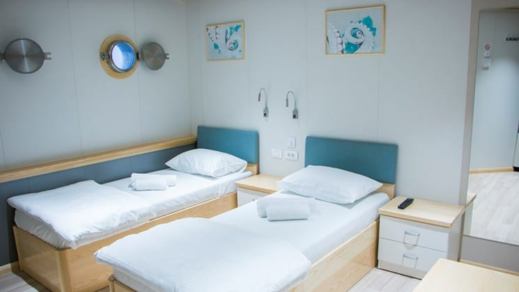 Fantazija stateroom with 2 twin beds, nightstand, seating with portholes.