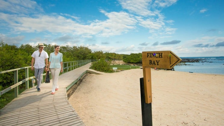 Man and woman walk on path near beach with sign pointing to Finch Bay near Finch Bay Eco Hotel in the Galapagos Islands