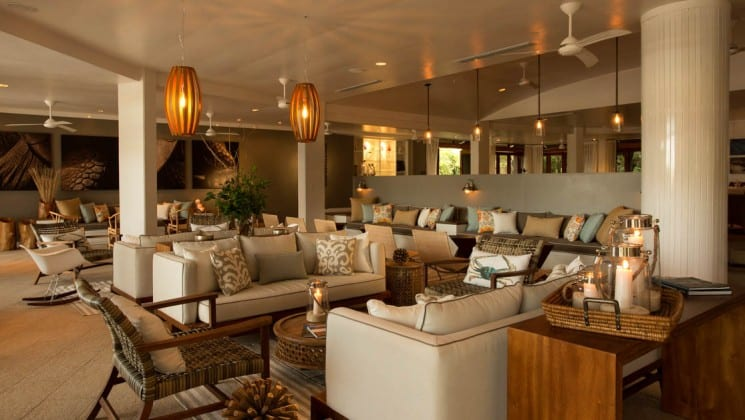 Lounge with couches, chairs, tables and abundant natural light at Finch Bay Eco Hotel in the Galapagos Islands