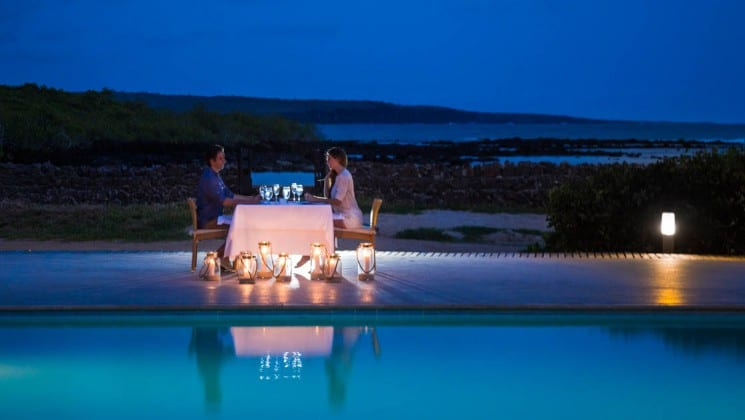Woman and man dining by candlelight near pool at Finch Bay Eco Hotel in the Galapagos Islands