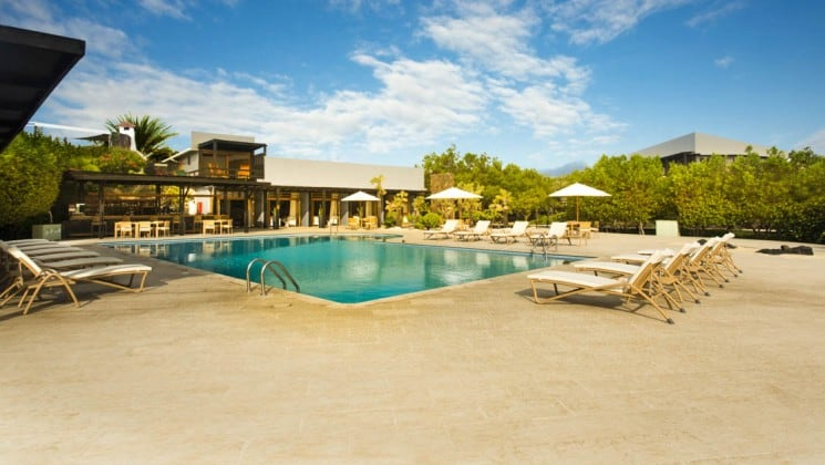 Large outdoor pool surrounded by lounge chairs at Finch Bay Eco Hotel in the Galapagos Islands