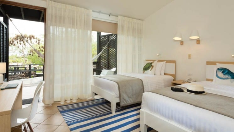 Two full beds in a room with desk and outdoor hammock at Finch Bay Eco Hotel in the Galapagos Islands