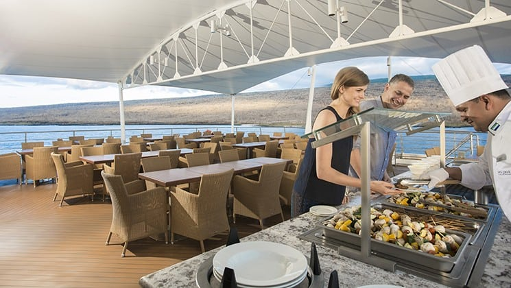 a couple receives buffet food from a chef on a covered area of the deck on the Santa Cruz II Galapagos small ship