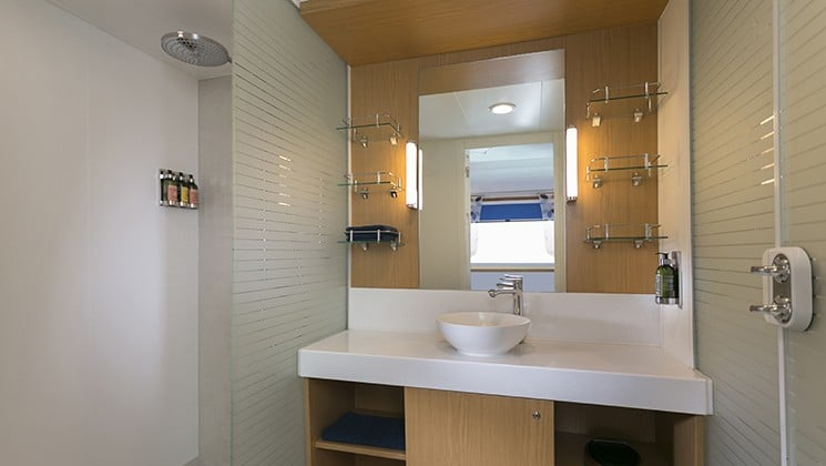 bathroom with white counter top, mirror and wood accents aboard the Santa Cruz II Galapagos small ship