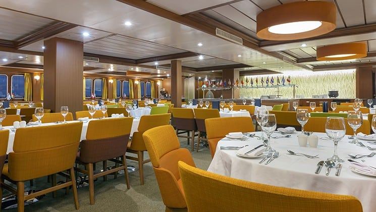 dining room with tables and chairs throughout aboard the Santa Cruz II Galapagos small ship
