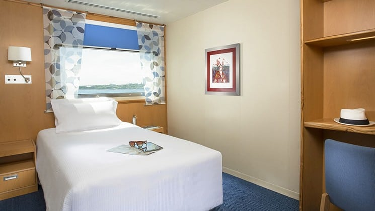 cabin with a single bed, picture on the wall and large window with curtains aboard the Santa Cruz II Galapagos small ship