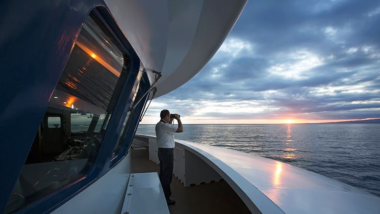 a man with binoculars looking out over the water during sunset aboard the Santa Cruz II Galapagos small ship