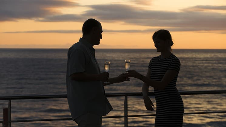 a couple cheers with champagne on the deck of the Santa Cruz II Galapagos small ship at sunset