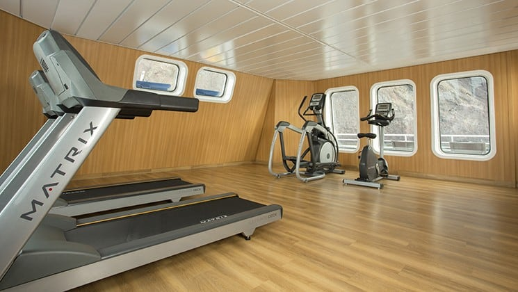 the gym aboard the Santa Cruz II Galapagos small ship with wood floors, exercise equipment and windows on both walls