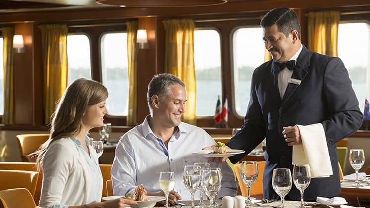 a baby boomer couple being served a meal by a crew member aboard the Santa Cruz II Galapagos small ship
