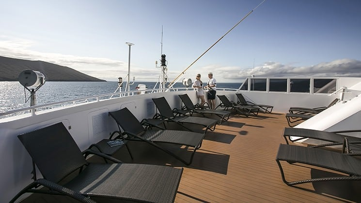 a row of lounge chairs on the sundeck of the Santa Cruz II Galapagos small ship on a sunny day