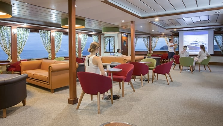 adventure travelers relaxing in an open room filled with different colored couches and chairs aboard the Santa Cruz II Galapagos small ship