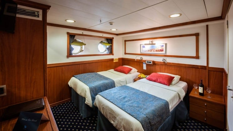 Galileo Category C stateroom with double bed, nightstand, closet, and 2 portholes.