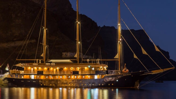 Galileo sailboat lit up at night while anchored off the Mediterranean coast.