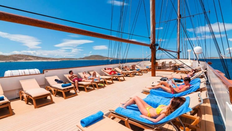 Galileo sundeck with passengers lounging in the sun on lounge chairs on the bow of the sail boat.